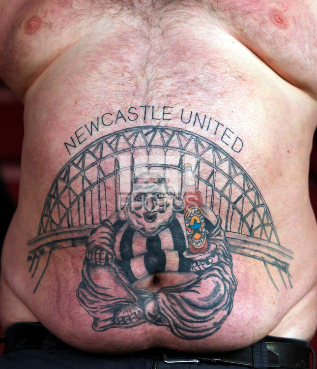 A Newcastle United fan sports a large tattoo on his stomach